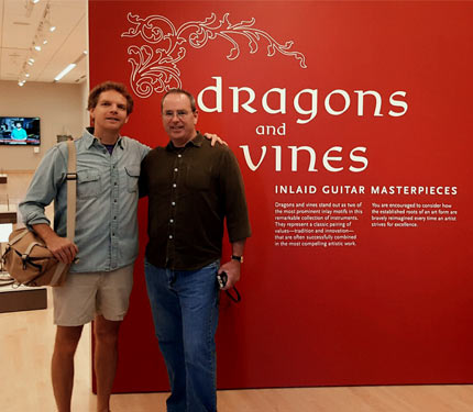 Bill Seymour with friend in front Dragons & Vines exhibit wall