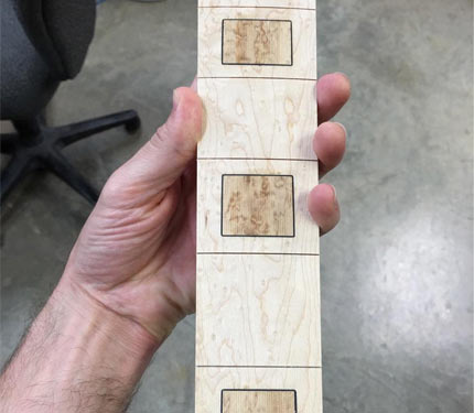 Hand holding an inlaid Elrick fretboard
