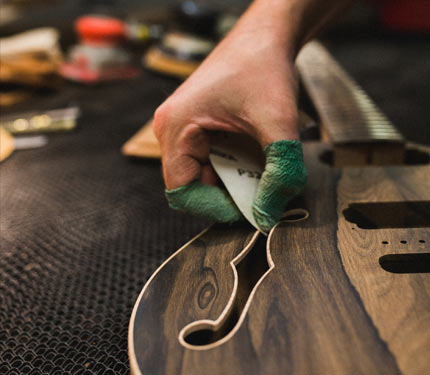 Hand sanding the guitar